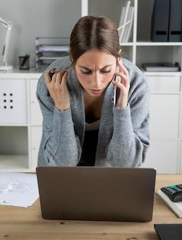 Средний выстрел женщина, глядя на ноутбук