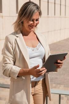 Женщина среднего выстрела, смотрящая на планшет