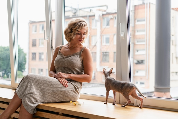 Donna del tiro medio che guarda il gatto
