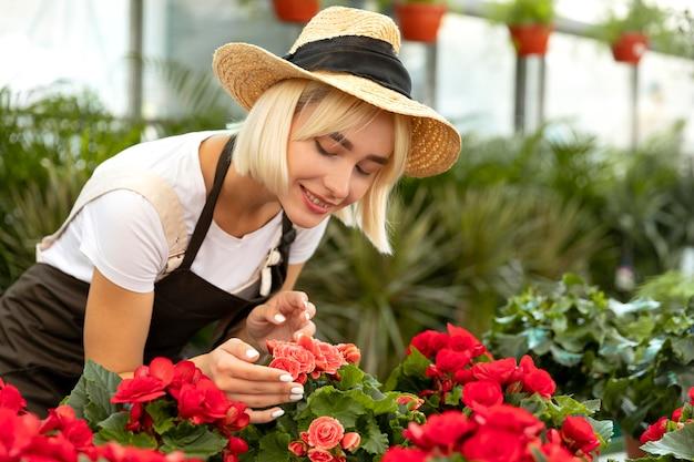 Donna del tiro medio che guarda i fiori