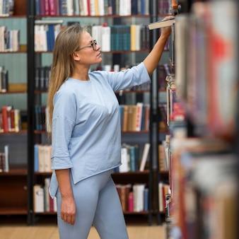本を探しているミディアムショットの女性
