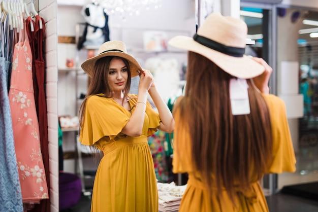 Средний выстрел женщина смотрит в зеркало