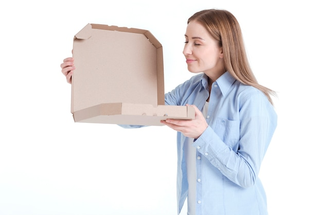 Medium shot of woman looking into a pizza box and smells