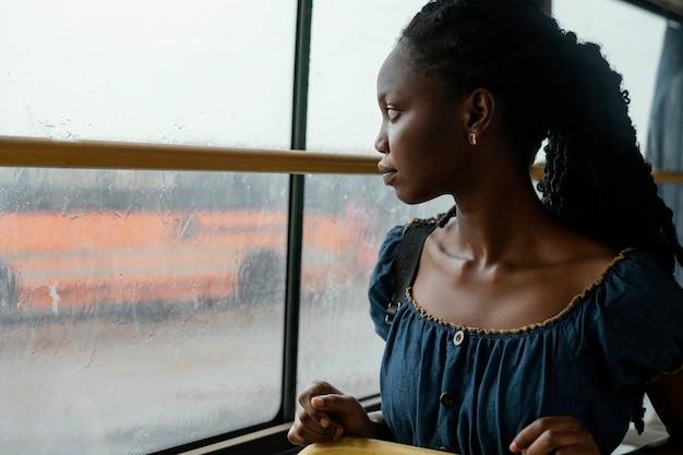 Donna del colpo medio che osserva fuori dalla finestra