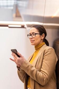 Medium shot woman looking at phone