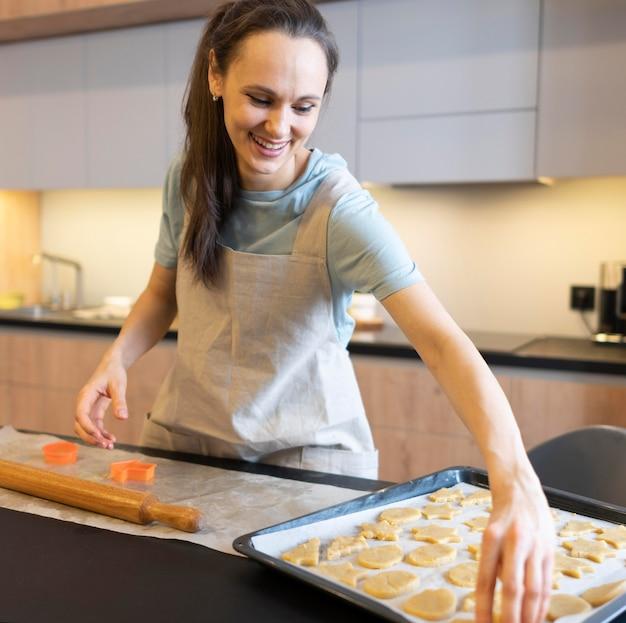 クッキーを作るミディアムショットの女性