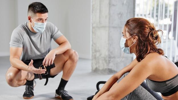 Medium shot woman and man wearing masks