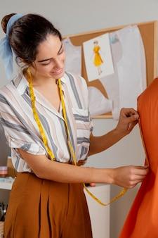 服を測定するミディアムショットの女性