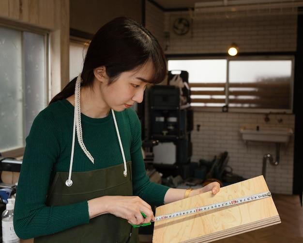 Colpo medio donna che misura il legno