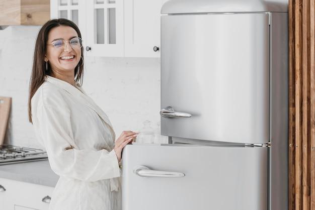 ミディアムショットの女性が冷蔵庫を開ける