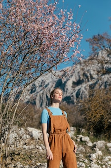 Medium shot woman in overall under blooming tree