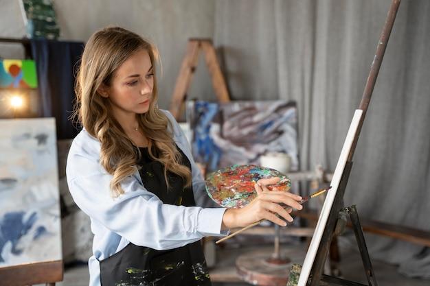 Medium shot woman painting on canvas