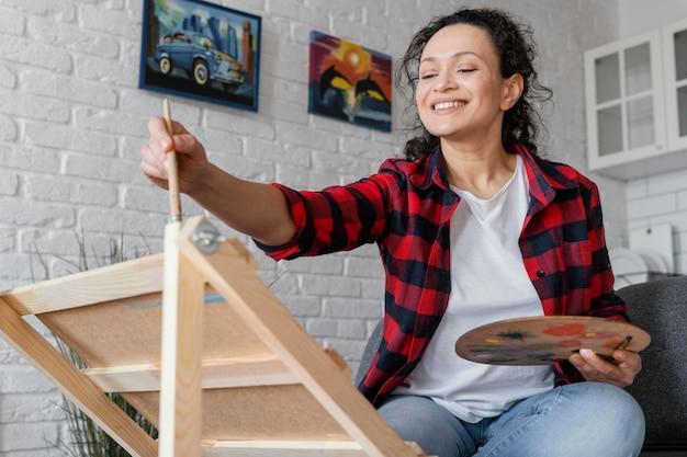 屋内で絵を描くミディアムショットの女性