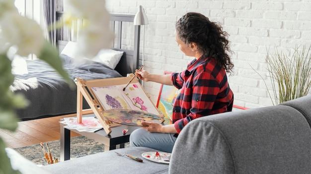 Женщина среднего кадра рисует в помещении