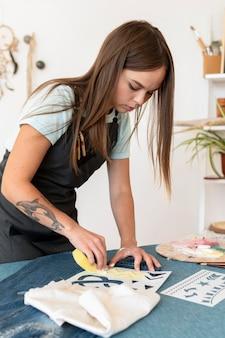 スポンジでジーンズを描くミディアムショットの女性