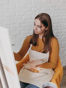 キャンバスに絵を描くミディアムショットの女性