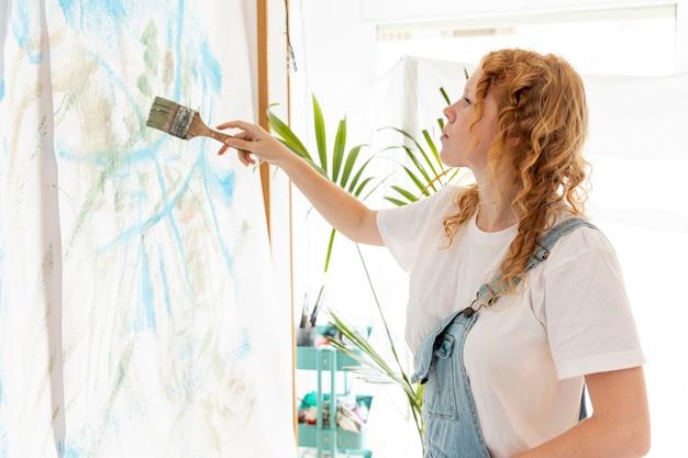 Средний снимок женщины, рисующей на стене