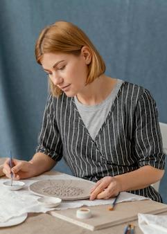 ミディアムショットの女性の絵画プレート