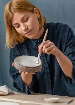 ミディアムショットの女性の絵画の花瓶