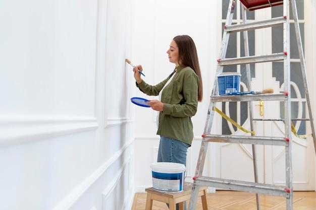 自宅で壁を塗るミディアムショットの女性