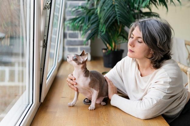 Средний выстрел женщина ласкает кошку