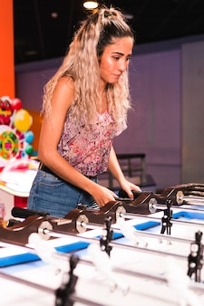 Medium shot woman playing foosball