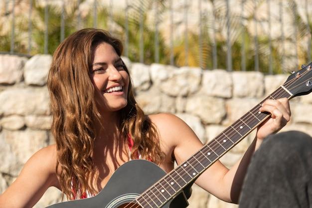 ギターを弾くミディアムショットの女性
