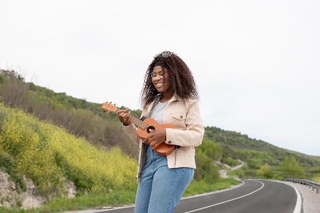 중간 샷 여자 기타 연주