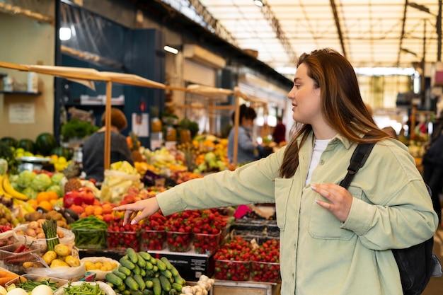 Женщина среднего выстрела, указывая на овощ