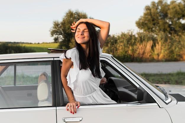 窓の外でポーズをとるミディアムショットの女性