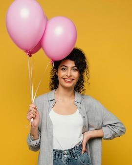 Среднего выстрела женщина позирует с воздушными шарами