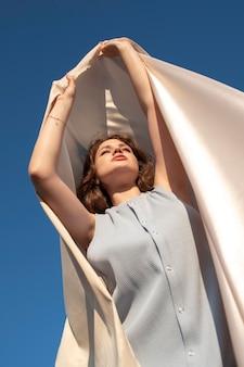 Medium shot woman posing with cloth