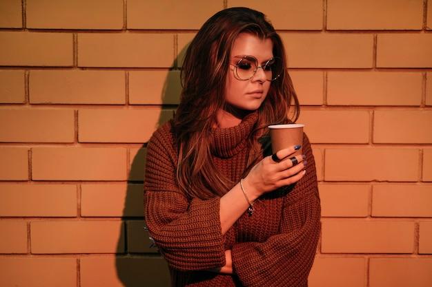 Donna del colpo medio che posa con la tazza di caffè
