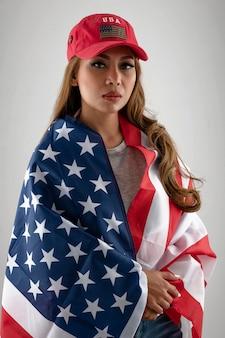 Среднего выстрела женщина позирует с флагом