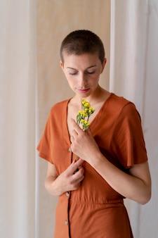 꽃과 함께 포즈를 취하는 미디엄 샷 여성
