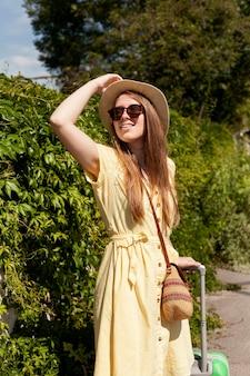 Средний выстрел женщина позирует в шляпе