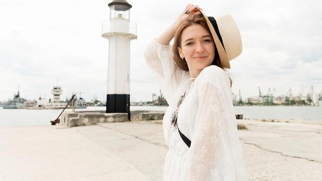 Medium shot woman posing with hat