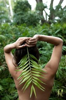 葉っぱでポーズをとるミディアムショットの女性
