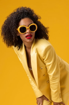Mediumshot woman posing with yellow sunglasses