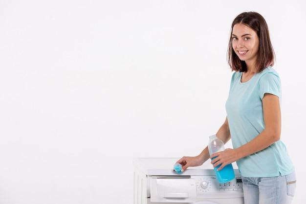 ミディアムショットの女性が洗濯機に洗剤を注ぐ