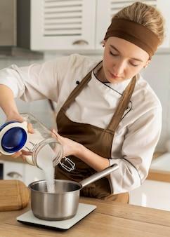 鍋に砂糖を注ぐミディアムショットの女性