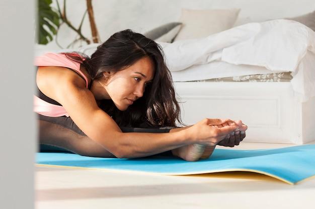 Medium shot woman practicing yoga