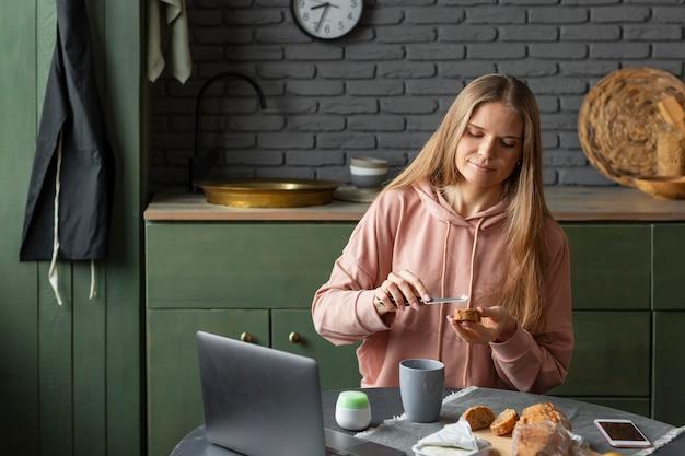 Donna del colpo medio che prepara la colazione