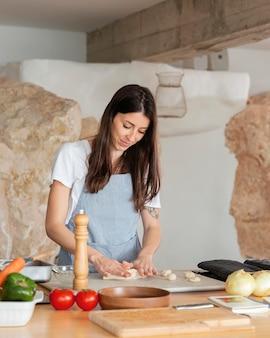 Женщина среднего выстрела готовит тесто