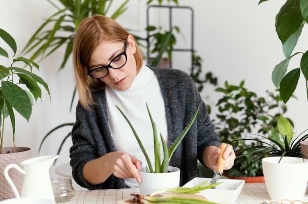 Medium shot woman putting soil in pot