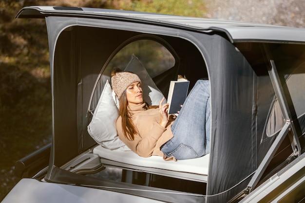 Средний снимок женщины, читающей книгу на природе