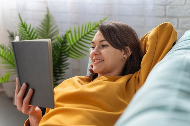 Medium shot woman reading on couch