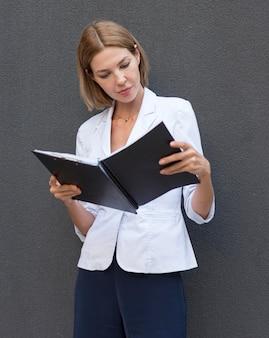 Medium shot woman reading documents