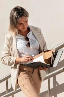 Женщина среднего кадра читает документы