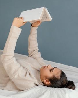 Средний снимок женщины, читающей в постели